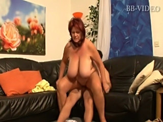 Big breasted older gal fucks young stud on the couch.