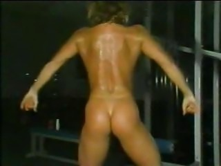 Sexy show of a beautiful body builder flexing her muscles in the gym