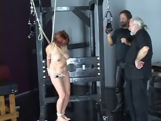 Nude redhead with nice tits and ass is whipped in bdsm dungeon