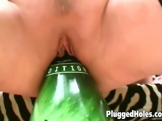 Slutty woman in sexy lingerie loves fucking a beer bottle on bed