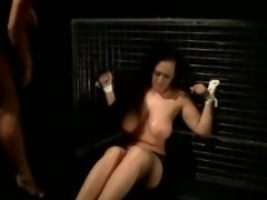 Tied down brunette subject gets her tits and legs flogged