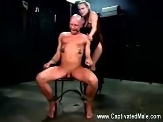 A slave gets his cock tied up by his domina