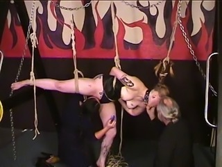 Cute young brunette in a corset is tortured by man and woman bdsm masters