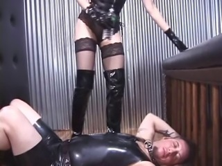 Man gets caged by dark dominatrix then must suck her stilettos to get her off