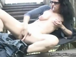 Slutty MILF Mina is a smoker and a rubber. She moves out onto her outdoors stairs, and lights one up. She strips out of her pants and finger fucks herself while smoking.