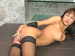 The pretty brunette pornstar Roxanne Milana in a stockings penetrates her pussy with a glass dildo