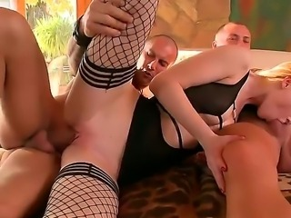 Petite pale blonde Gitta Blond with heavy make up and long sexy nails in fishnet stockings takes on two meaty peckers and gets her shaved twat banged balls deep.