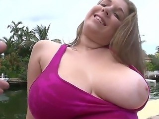 Young blonde is revealing a pair of her huge boobs for her lover by the pool
