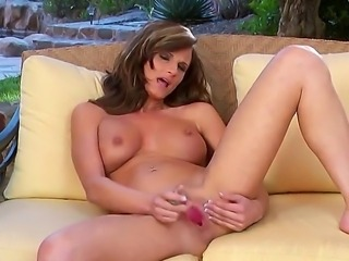 The ardent milf Daisy Lynn with the entrancing tits sucks her glass dildo and penetrates her vagina