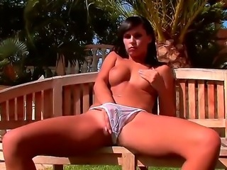 Hot and horny brunette Carie enjoys in playing with her body outdoor in the garden on the bench