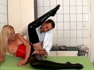 Kathia Nobili awaits doctor on her knees in his examining room. He soon returns to gauge her oral abilities with a shiny black butt plug, which he has her lubricate with her saliva. T