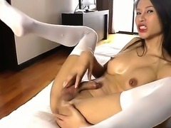 This ladyboy lies back in her comfy bed, her semi-hard cock nestling against...