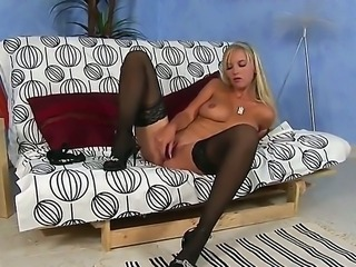 The naughty blonde whore Chikita in black stockings penetrates her peach with a dildo