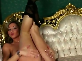 Ensconced on the luxury armchair, naughty milf blonde Carolyn Cage in super sexy stockings masturbates her still tight and gentle pussy with her fingers. Babe masturbates in her favorite pose.