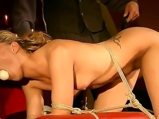 kinky beauty Joanna gets tied down in doggy style to have her holes used. First a carrot is shoved into her mouth followed by a ball. Then her torturer plays with her pussy