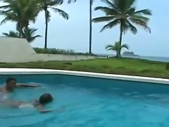 Tony Tigrao and this well-tanned Latina babe Karrol are swimming in a pool...
