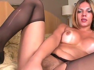 Big breasted shemale babe Raissa Nevada wears expensive black stockings on her bed as she grabs her large meat rod and strokes it passionately until she reaches an orgasm.