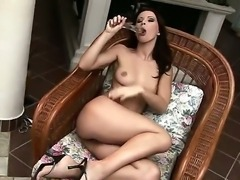 Sexy brunette with pierced pussy lips is drilling her vagina with a glass dildo