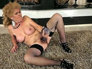 Busty grandma Effie shoves a new dildo in her shaved pussy in front of the fireplace
