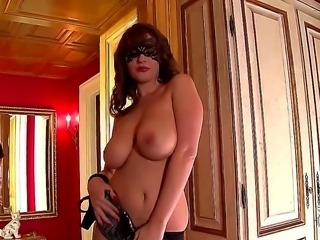 Turned on playful and experienced brunette milf LaTaya Roxx with red nails and arousing mask in sexy lingerie and high heels reveals her big juicy knockers while teasing in close up
