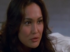 Tia Carrere showing some nice cleavage in a low-cut dress and various bikinis...