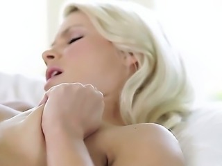 Young looking cute blonde babe Anikka Albrite with long legs and natural boobs spreads hot legs and enjoys fingering wet hairless fish lips to orgasm in bedroom in close up.