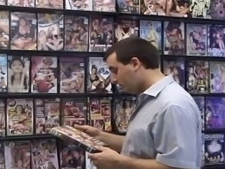 DVD shop turned into a sex playground for a horny couple. Girl got down and sucked hard erection until he jizzed all over her lusty face