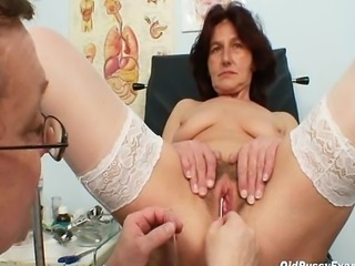 Pervy woman doctor examines hairy pussy grandma who is sitting on gyno chair with open legs. The doctor opens her hairy pussy with metal gyn tool called a speculum. Afterwards, he injects white healthy liquid into her old hairy pussy.