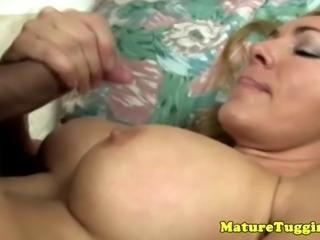 Blonde mature enjoys tit fuck session as she rubs guys dick