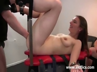 Skinny blond slut tied to a bench in a room full of perverts takes a monster...