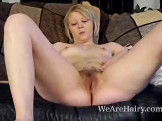 Danniella is a sexy blonde beauty laying on the couch when she starts stripping out of her clothes and her black and white lingerie and then she takes her fingers and plays with her warm hairy pussy.