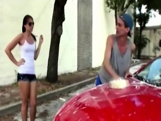 Brunette jerks a guys cock off while sitting on a sports car