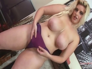 Curvy blonde chick Raphaella Lily stripping to show off her giant boobs and pink pussy