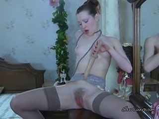 Ambrose enjoys watching her dildo slide in and out of her hairy pussy while she rubs her clit and her soft tits