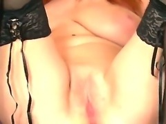 Redhead Marina Visconti  in black nylons shows off her massive tits as she...