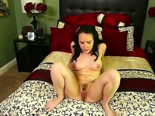 Completely naked brunette Katie St. Ives with natural titties strokes her pink puffy pussy like crazy on the edge of the bed before she gets her mouth filled with hard throbbing dick.