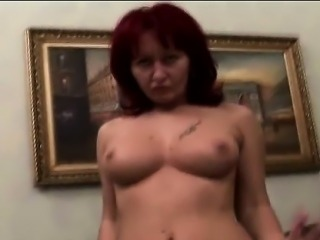 Redhead mature caregiver plays lonely on the couch