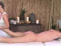 Classy masseuse oils up before jerking cock