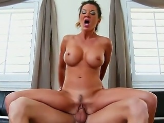 Raquel DeVine is pulling a cock with her mouth and is sucking it dry. She is seen on the sofa with her sons friend that has come over for a visit. She is giving a blow job.