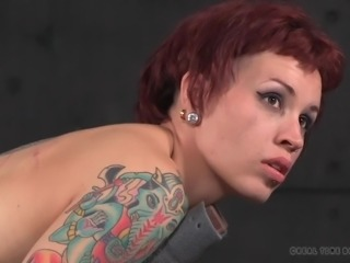 Bounded redhead babe is placed in a wooden device and brutally fucked with a...
