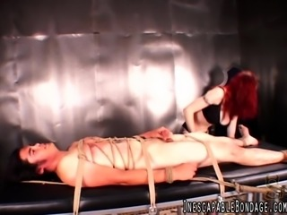 Flame-haired dominatrix Berlin strokes her pussy with a vibe beside her bound slave