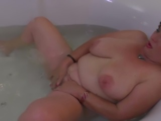 Fatty slides into the bathtub and makes her pussy feel good