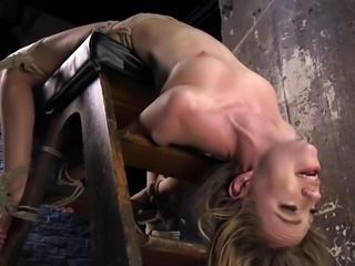 Watch pretty blonde babe Lyra Law, placed on a special bondage device head...
