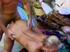 She licks his nut sack and gets drilled doggy style in the pool