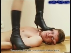 Sexy black leather boots on the mistress trampling him