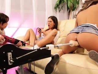 Three sensuous lesbians having fun with mechanical toys on the couch