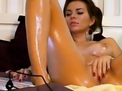 Provoking brunette with big boobs oils up her body and rubs