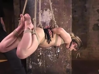 Goldie gets gagged, hogtied, and put up in the air to swing. Her executor puts on some nipple clamps next, adding to the pain part some more. She mumbles her approval through the gag, when he fingers her pussy.
