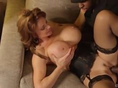 Lingerie-clad cougar with massive fake tits sucking a big black cock