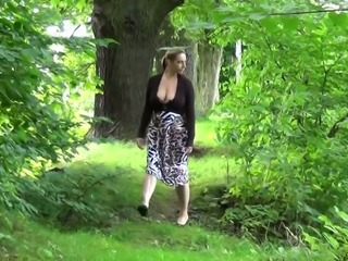 Busty white babe pulls up her skirt and pisses in the woods